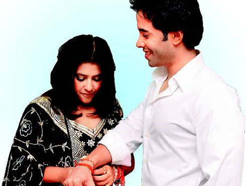 Bollywood brothers and sisters : Ekta Kapoor ties rakhi to brother Tusshar Kapoor.
